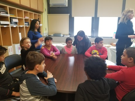 students sitting around a table waiting to speak
