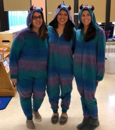 Three teachers dressed as dragons.