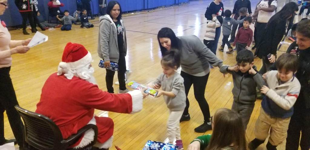 Teacher supports student to speak to Santa