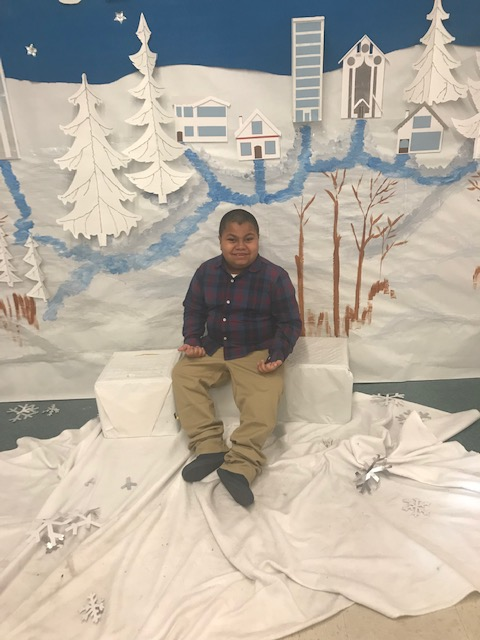 Student sits in snow scene holiday display