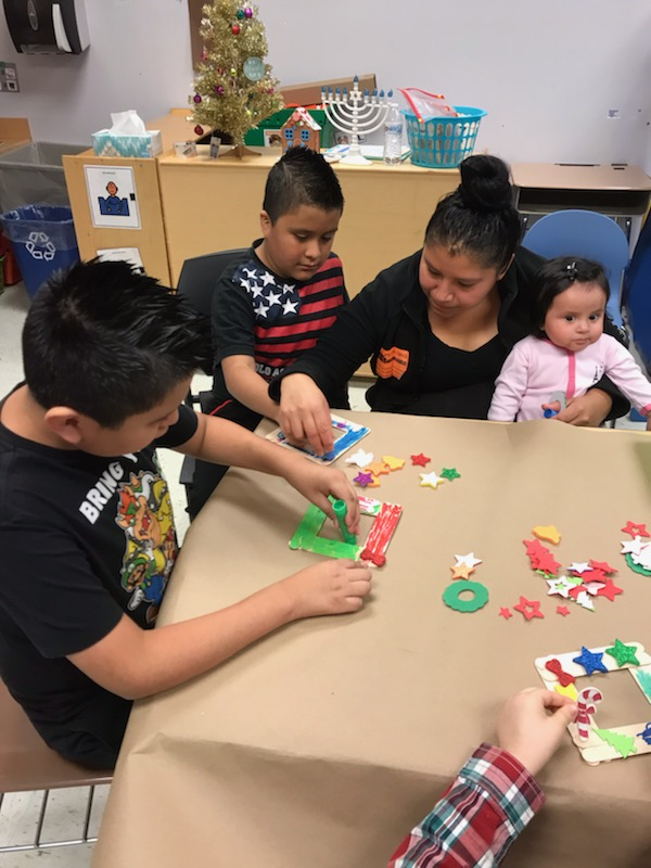 Parents and siblings participate in holiday crafts.