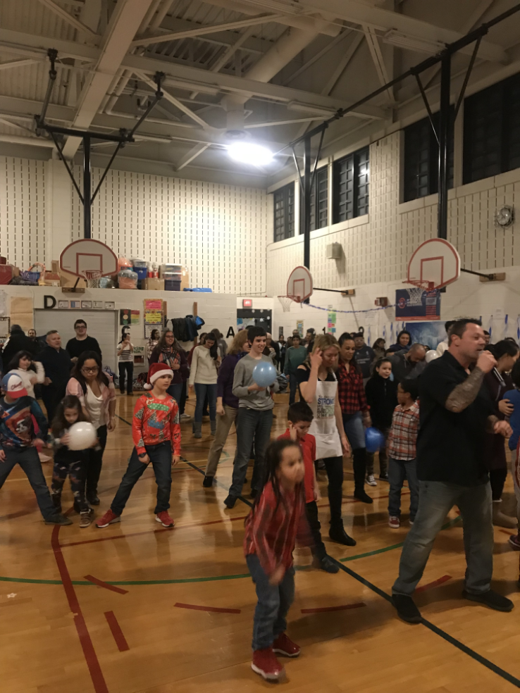 Children dancing in a school gym.