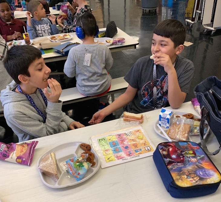 2 students engage in conversation at lunchtime during National No One Eats Alone Day.