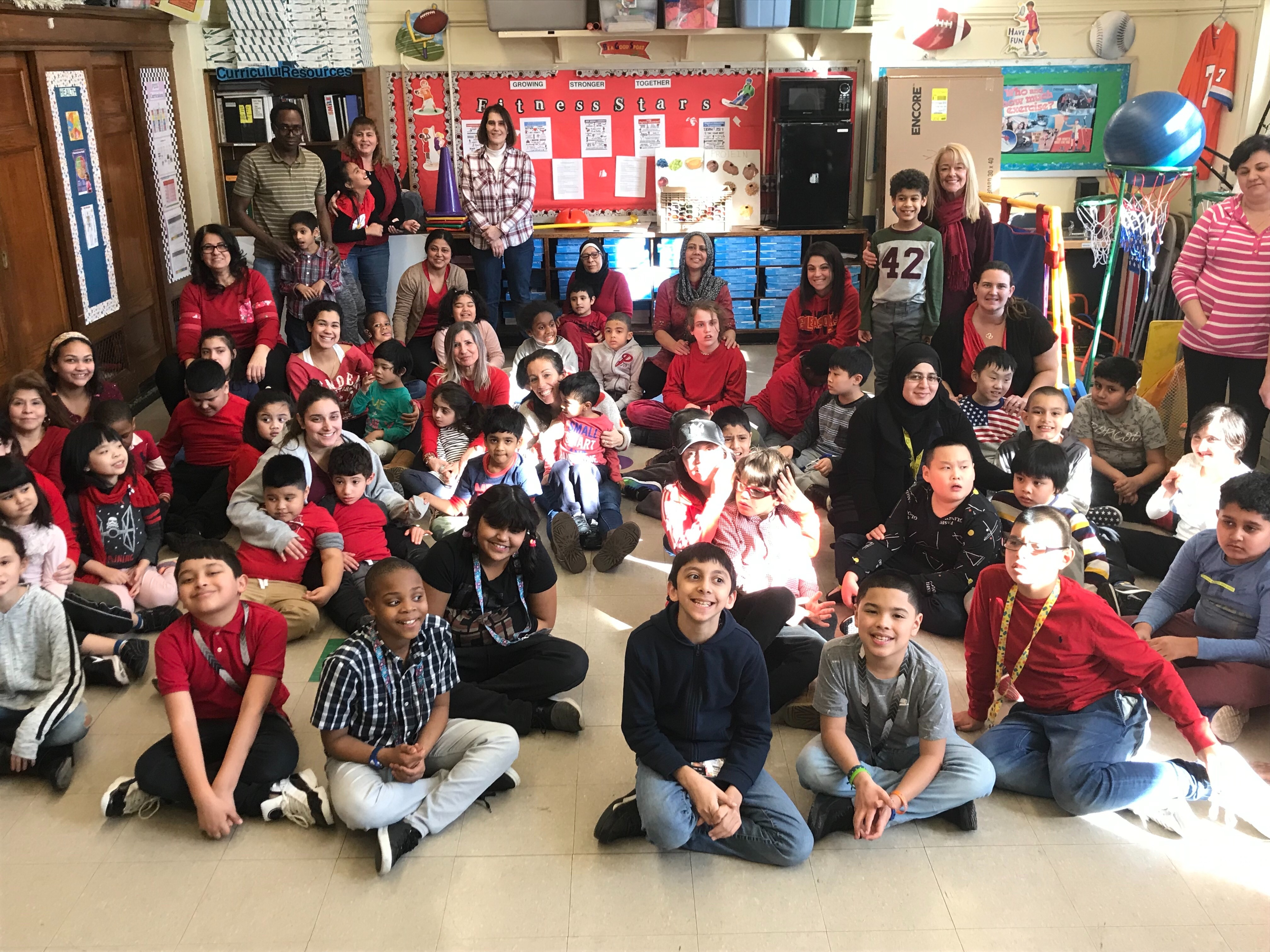 students and teacher group picture wearing red
