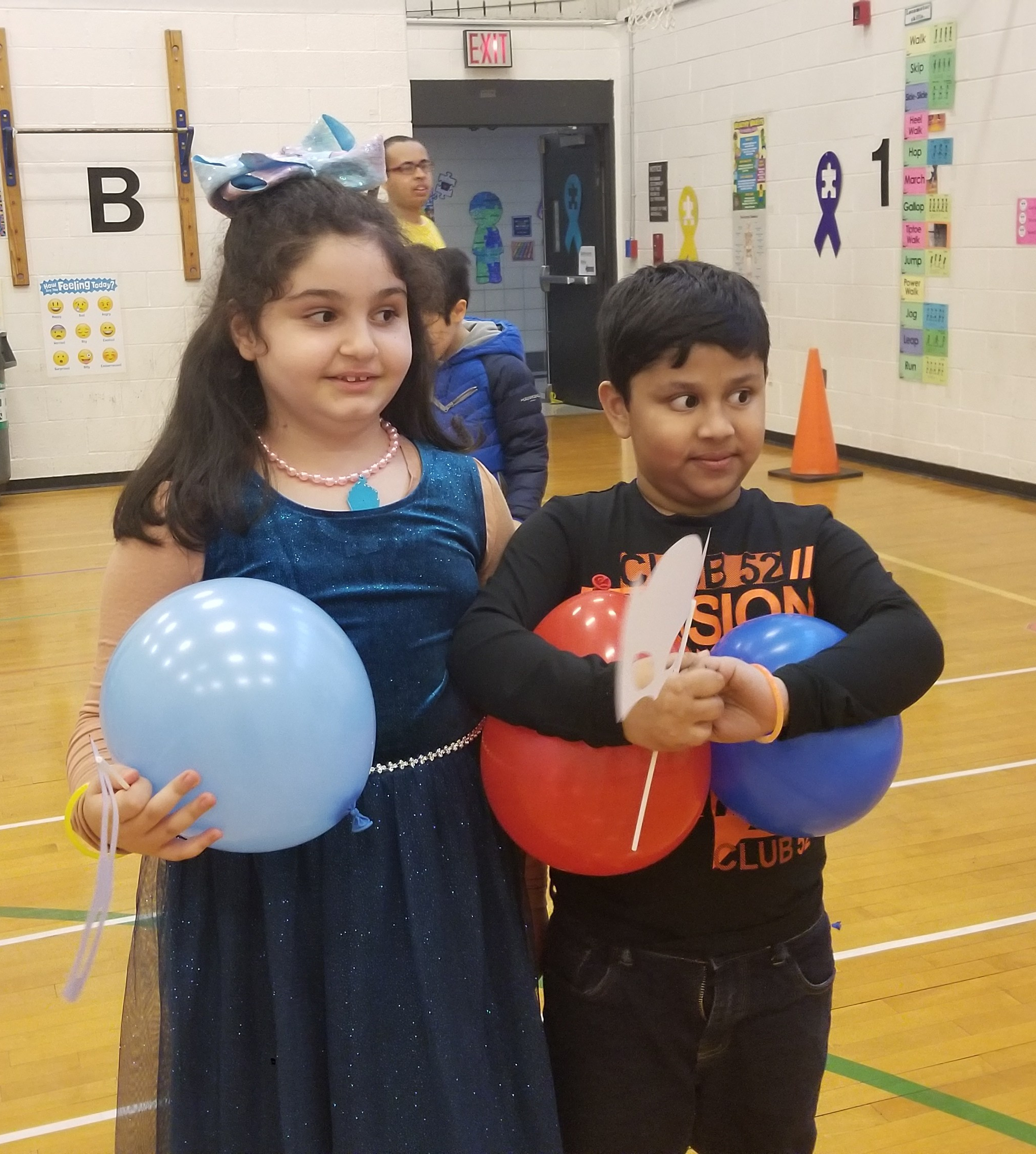2 Students enjoying balloons and dancing in the gym.