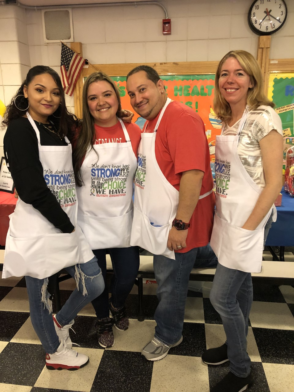 three women and a man smiling wearing aprons