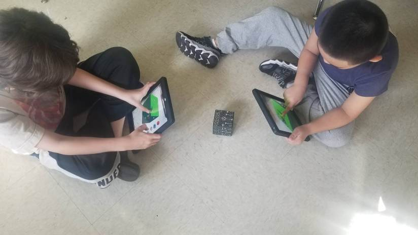 Two boys play with iPads and AR cube