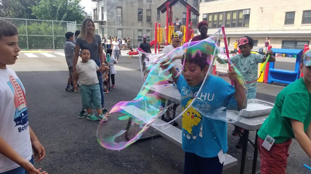 Boy blows into giant bubble.