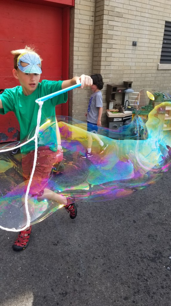 Boy makes giant bubble while running