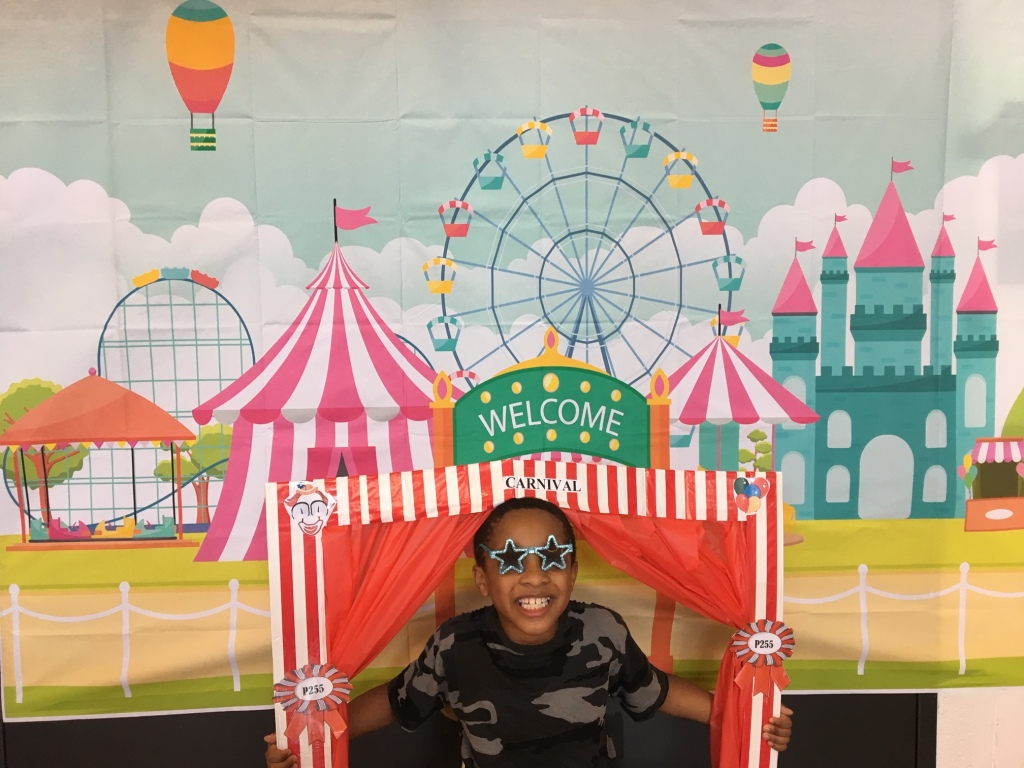 Boy wearing shades appears in theater prop as if on stage. Backdrop is ferris wheel and big top.