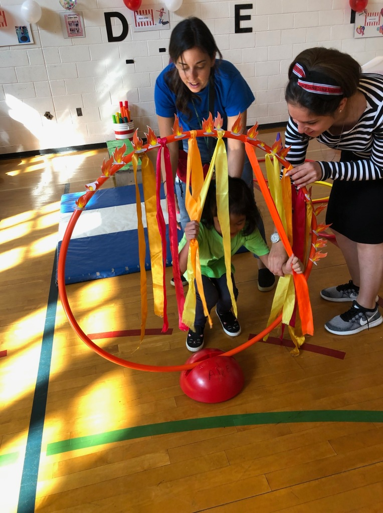 Children play with hoops and ribbons.