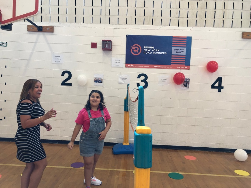 Teacher and student play volleyball with balloons