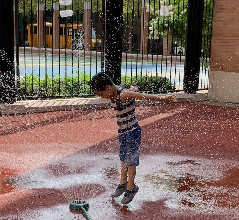 Child jumping in sprinkler