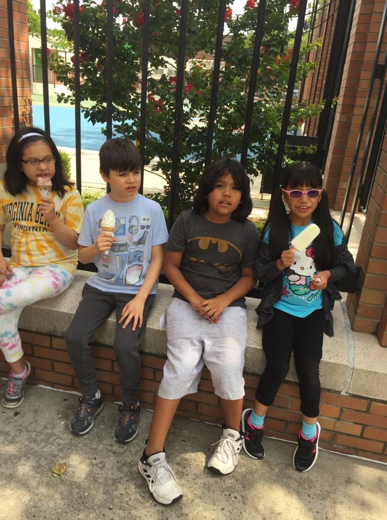 Four children sit and eat ice cream