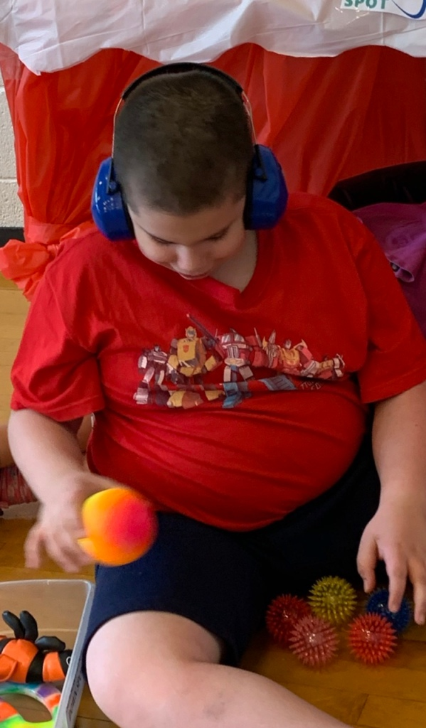 Boy wearing headphones plays with sensory balls.