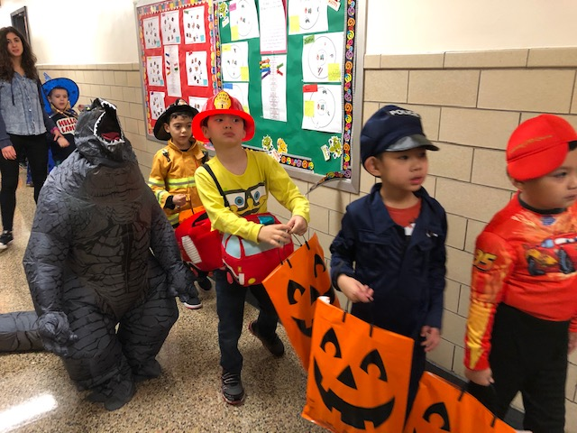 Small children carrying pumpkin bags dressed up as Lightning McQueen, a policeman, firefighters and a dinosaur.