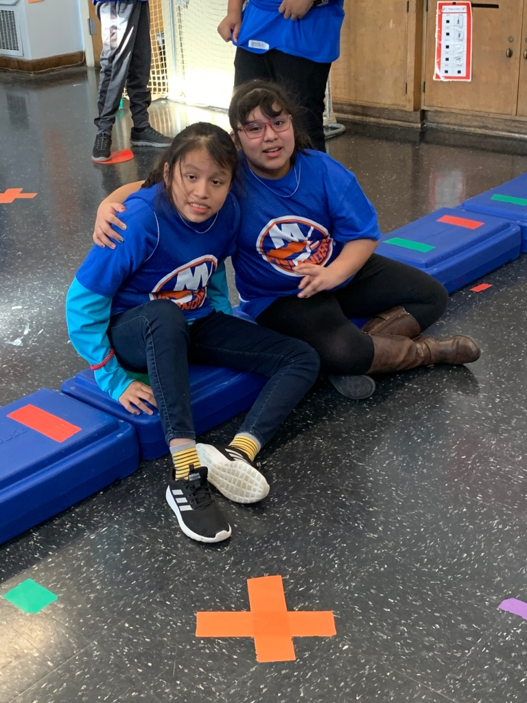 Two girls sitting in Islanders shirts with arms around one another