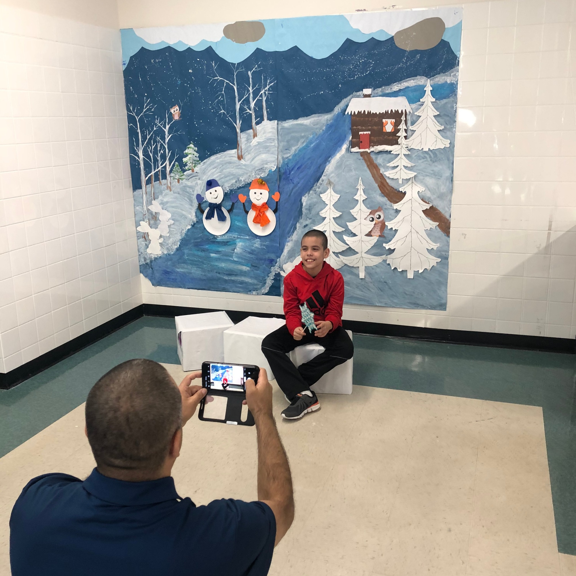 Father takes photo of student by our winter scene.
