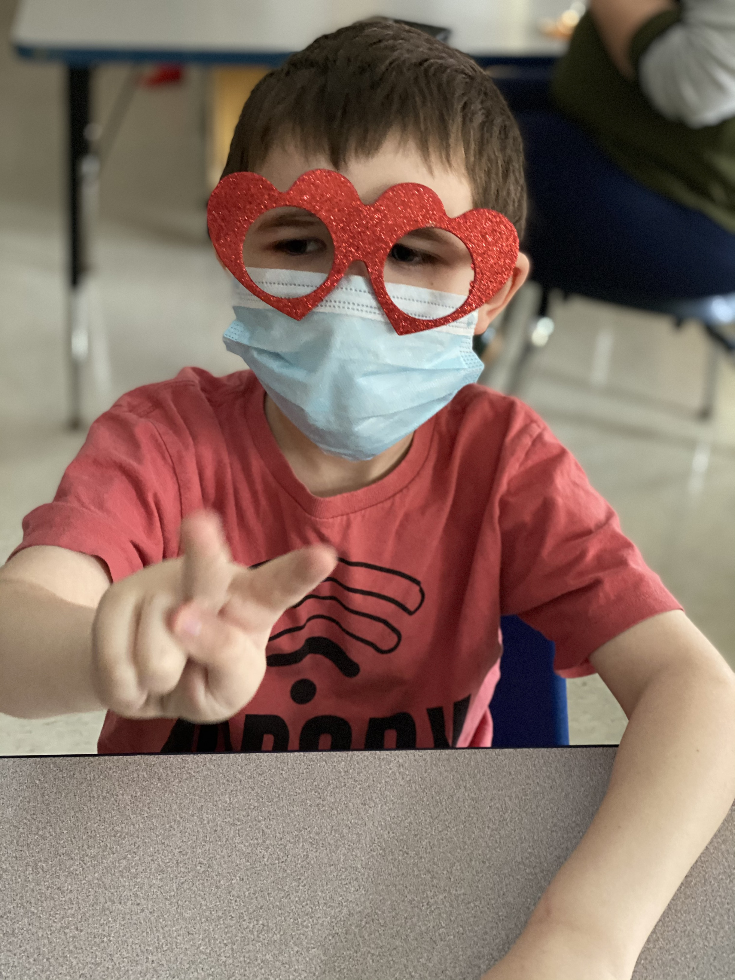 child with heart sunglasses and mask