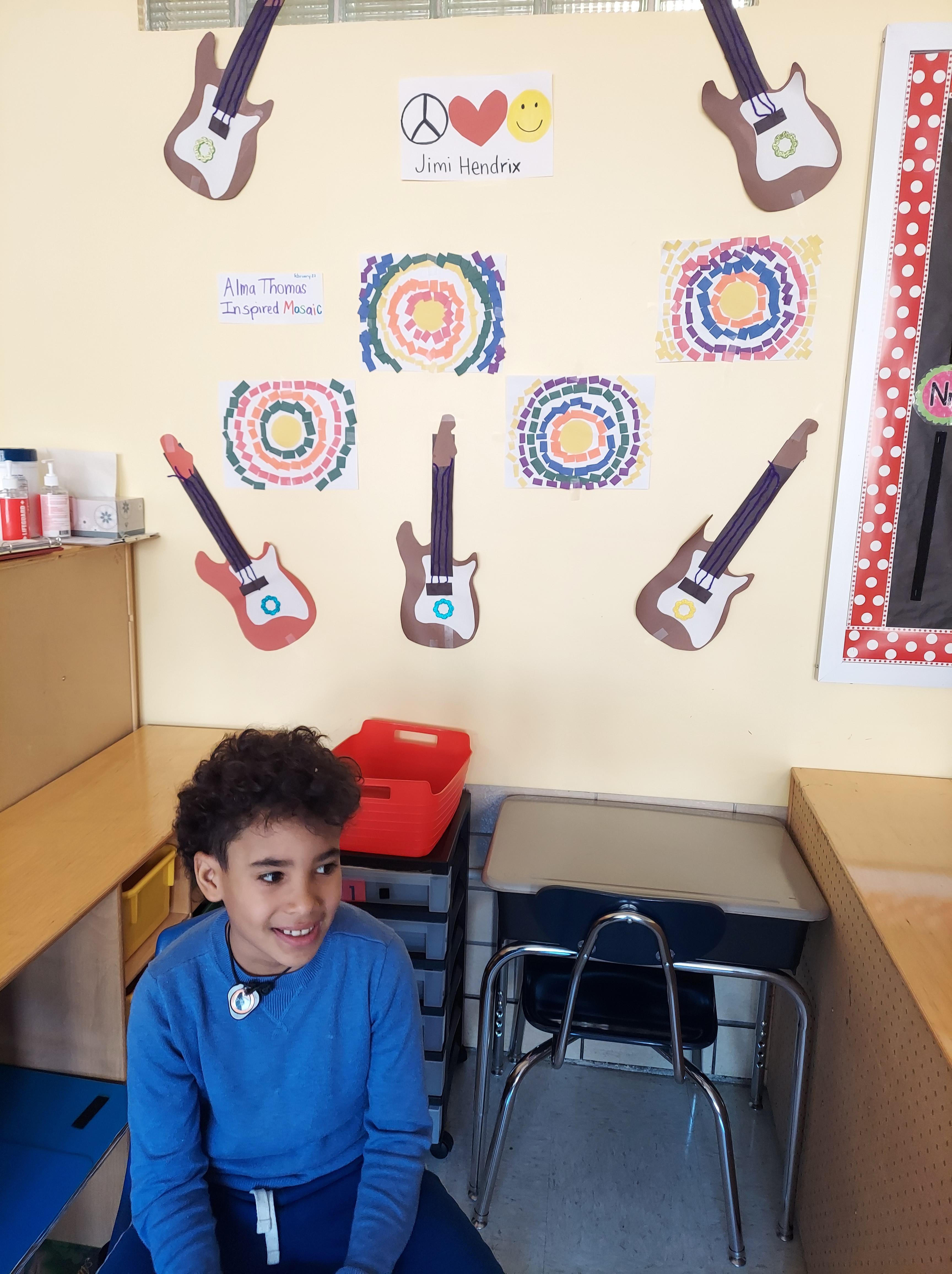 Child sitting in front of black artist crafts.