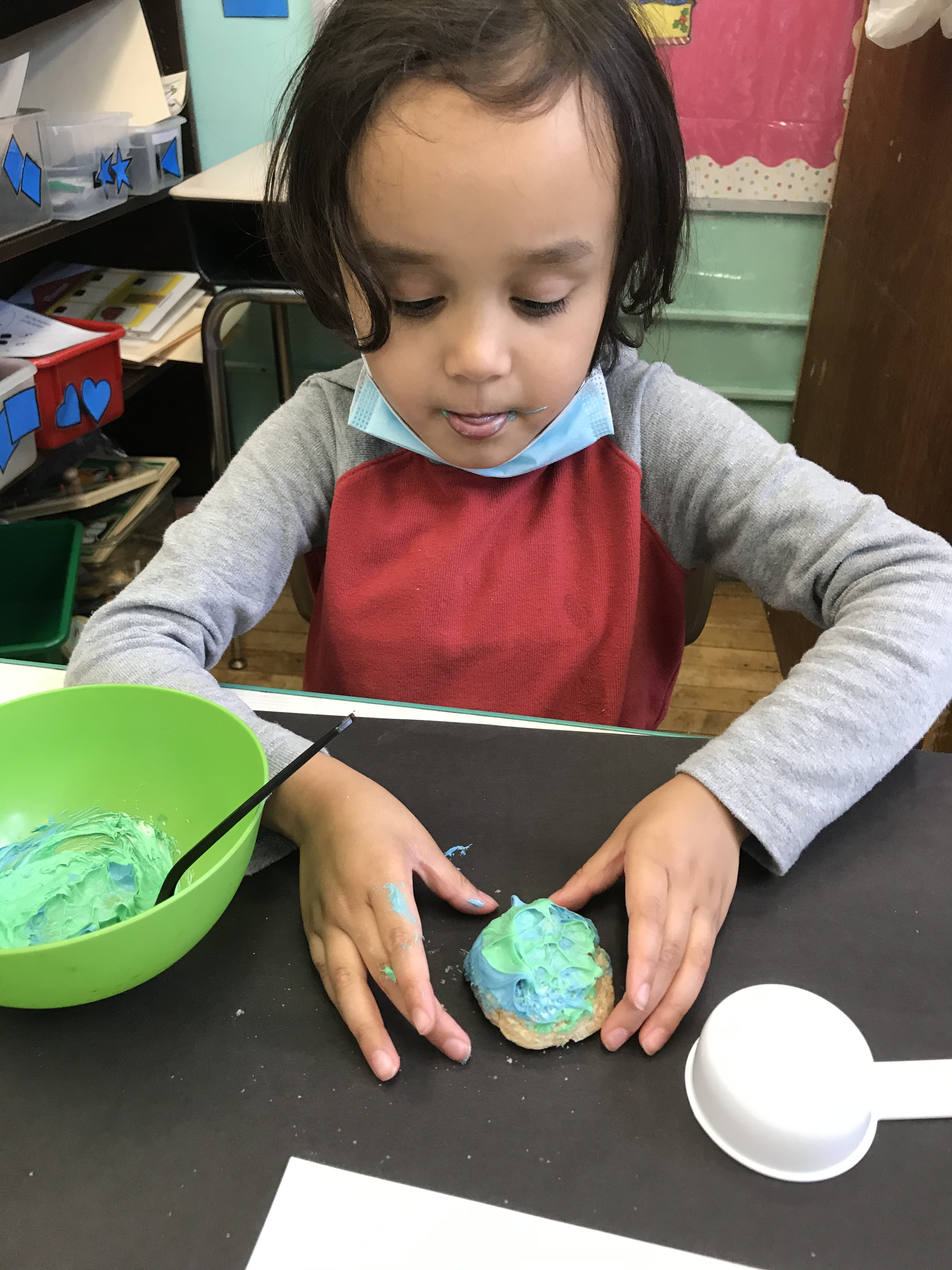 Putting green and blue frosting on an earth day cookie